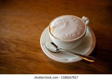 Fresh hot Coffee by top view on wooden table.cappuchino coffee in white porcellan cup and saucer with silver spoon.Minimal composition, hipster vibes. Top view, flat lay copy space for your text.