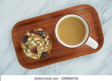 Fresh hot coffee and pecan oat chocolate muffin on small wooden tray shot from overhead.  Healthy and nutritious snack.