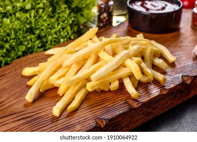 Fresh hot french fries with salt vegetables and spices on a dark concrete background