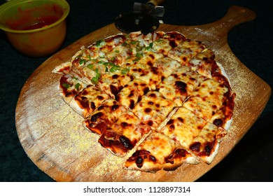 Fresh hot homemade pizza right out of the oven and cut into square pieces.