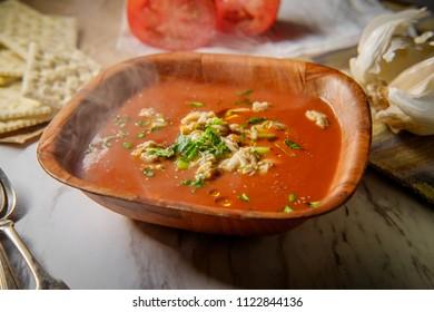 Fresh hot Manhattan Clam Chowder soup with soda crackers and parsley garnish