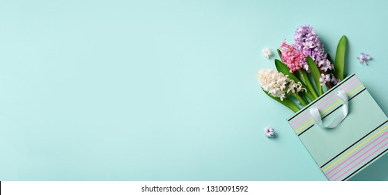 Fresh hyacinth flowers in shopping bag on blue punchy pastel background. Banner with copy space. Spring, summer, Woman day concept. Creative layout. Top view, flat lay