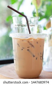 Fresh ice coffee in plastic glass on table with blur green plant background.  Relaxing life style with cold beverage.