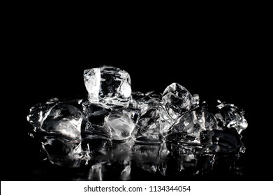 Fresh ice cubes arranged in pile and slowly melting on the dark background of studio