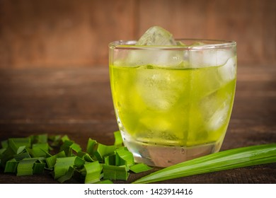 Fresh Ice pandan drink on the wood table there are pandan leaves and slice pandan placed around.