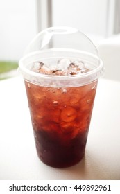 Fresh ice tea in plastic glass with straw
