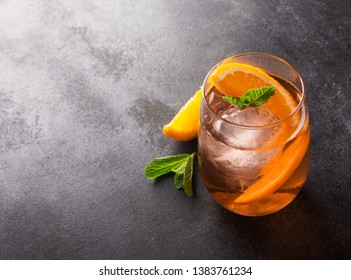 Fresh ice tea summer cocktail with orange, mint and ice in glass on dark background
