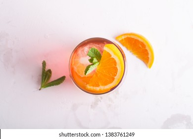 Fresh ice tea summer cocktail with orange and ice in glass on white background. top view