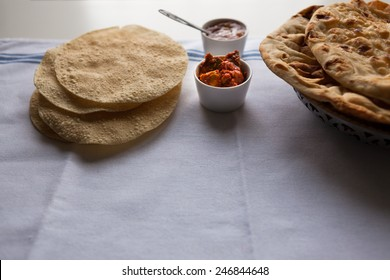 Fresh Indian flat breads nan and poppadom served with mango chutney and pickle on the table