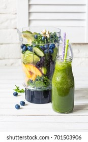 Fresh ingredients in a blender for making smoothies and healthy green smoothie in bottle with straw.