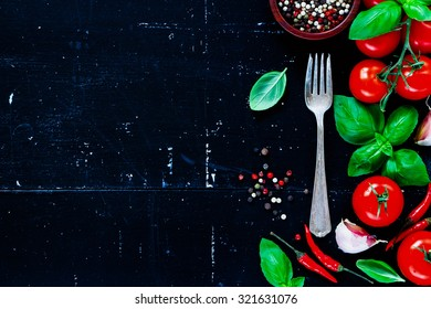 Fresh ingredients (cherry tomatoes, spices, garlic and basil leaves) on dark vintage background with space for text. Still life, vegetarian food, health or cooking concept.