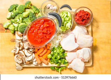fresh ingredients for chicken cacciatore  on the block ready to cook