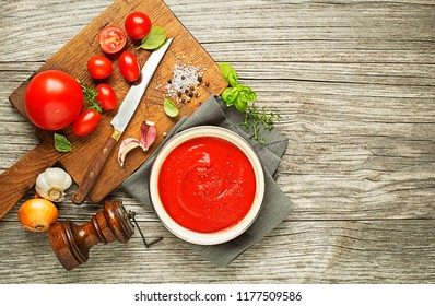 Fresh ingredients for cooking tomato sauce on wooden background place for text. Vegan food vegetarian and healthy cooking concept.