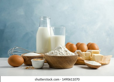 Fresh ingredients for delicious homemade cake on white wooden table against blue background - Shutterstock ID 1490611070