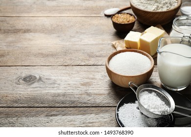 Fresh ingredients for delicious homemade cake on wooden table. Space for text