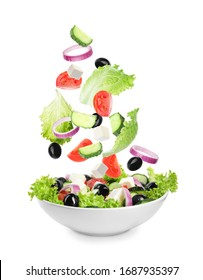 Fresh ingredients for Greek salad falling into bowl on white background - Shutterstock ID 1687935397
