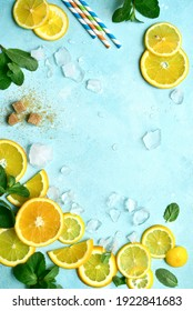 Fresh ingredients for making citrus lemonade : lemons, mint, sugar, ice cubes on a light blue slate, stone or concrete background. Top view with copy space.