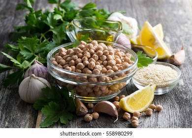 fresh ingredients for preparing hummus on wooden background, closeup