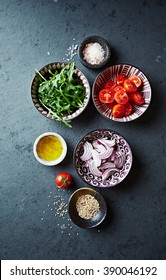 Fresh ingredients for salad; juicy cherry tomatoes, fresh rocket, red onion, flax oil  and sesame seeds in small ceramic bowls on dark stone background. Concept for healthy nutrition. Top view.