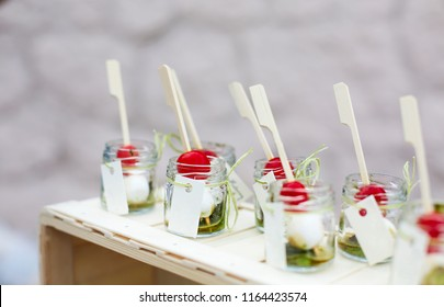 Fresh italian caprese salad with mozzarella and tomatoes in little jars. Finger food on catering event. Shallow focus