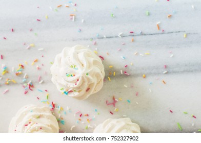 Fresh italian french meringue cookies with colorful sugar sprinkles on marble table