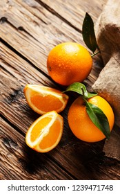 Fresh Italian oranges with green leaves on the wooden table