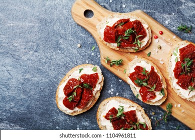 Fresh italian sandwiches with cream cheese and sun dried tomatoes on wooden kitchen board top view. Delicious snack and appetizer.