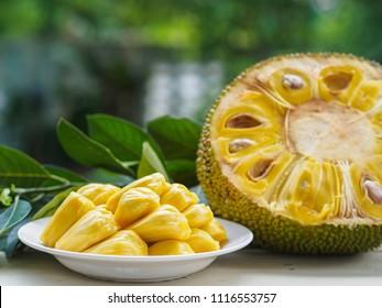 Fresh Jackfruit in white dish, half of jack fruit and jackfruit leaf on wooden table.
