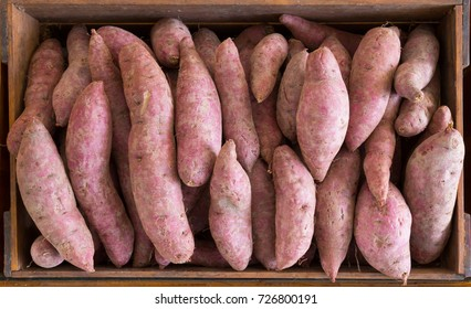 fresh Japanese sweet potatoes in wooden box, top view image