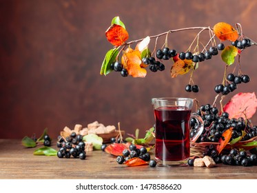 Fresh juice of  black chokeberry (Aronia melanocarpa) in glass and berries with leaves on wooden background.