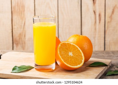 Fresh juice, a glass of orange juice and fresh oranges on the table