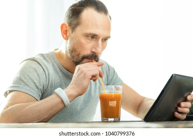 Fresh juice fresh news. Interested focused unshaken man spending time in the spacious room drinking juice and looking at the tablet.