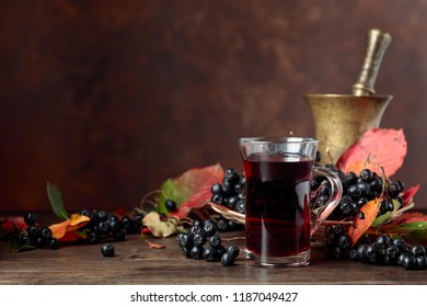 Fresh juice of ripe black chokeberry (Aronia melanocarpa) in glass and berries with leaves on wooden background.