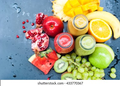 Fresh Juice Smoothie Color Tropical Fruits Strawberry Water Melon Kiwi Apple Orange Mango Banana Pine Apple Grape Pomegranate Bottles Top View Black Background Selective Focus