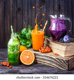 Fresh juice and smoothies with berries, fruits and green spinach on wooden background