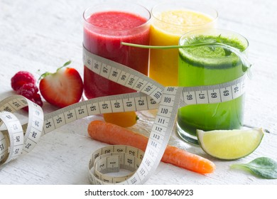Fresh juices measuring tape fruits and vegetables lose weight diet concept