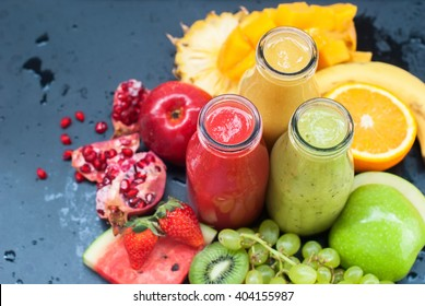 Fresh Juices Smoothie Three Bottles Red Green Orange Tropical Fruits Water Melon Strawberry Apple Kiwi Grapes Orange Mango Banana Pine Apple Pomegranate Grape Selective focus