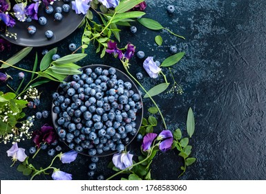 Fresh juicy blueberries on a black plate. Summer still life with blueberries, colored sweet peas and meadow grasses. View from the top.