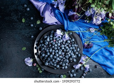 Fresh juicy blueberries on a black plate. Summer still life with blueberries, colored sweet peas and meadow grasses on a dark blue background. View from the top.