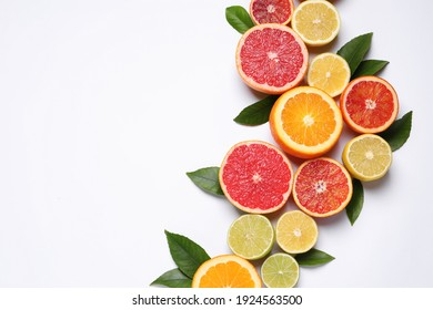 Fresh juicy citrus fruits with green leaves on white background, flat lay. Space for text