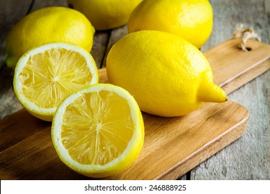 Fresh juicy lemons on a cutting board on a rustic wooden background