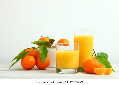 Fresh juicy mandarins and glass of juice on wooden table on white background. Concept tangerine juice.