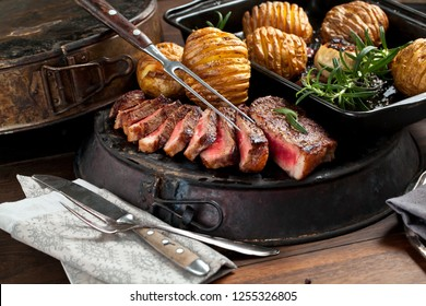 Fresh Juicy Medium Rare Beef Drillsteak with backed patatoes. Barbecue Meat Close Up