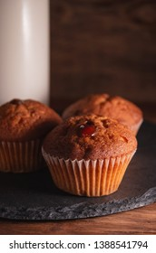 Fresh juicy muffins and a glass of milk on rustic wooden background