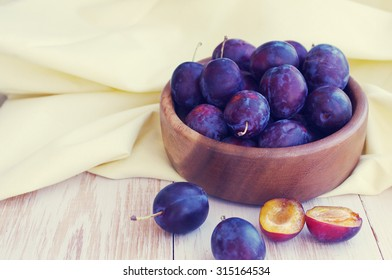 Fresh juicy plums in a wooden round plate. Crop of plums