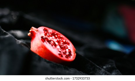 Fresh juicy pomegranate piece on dark background, healthiest fruits, food Against Breast Cancer