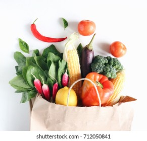 Fresh and juicy raw vegetables in a paper shopping back. White background. Broccoli, spinach, corn, tomatoes, chilling pepper,. Top view, side view. Vegetarian food