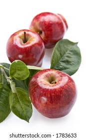 Fresh juicy red apples with green leaves