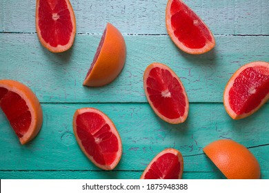 Fresh, juicy and sliced grapefruits isolated on green wood background