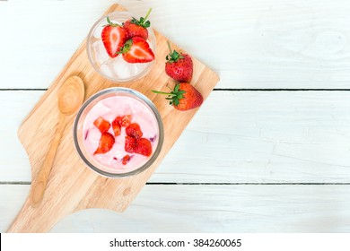 Fresh juicy strawberry with yogurt in a glass bowl and fresh strawberry on ice serving wood platter ; top view